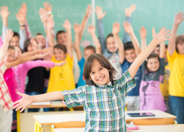 happy-children-group-with-arms-outstretched-school-classroom_21730-4357